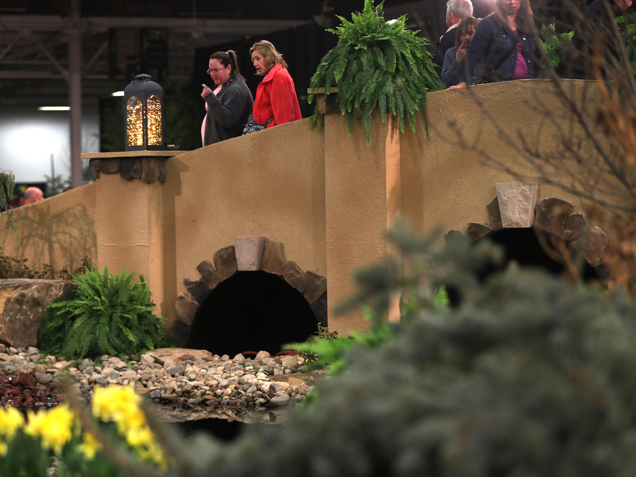 People visit the Pro Care Horticultural Services display which includes a bridge, at the Indiana Flower + Patio Show, at the Indiana State Fairgrounds, Sunday, March 10, 2019.