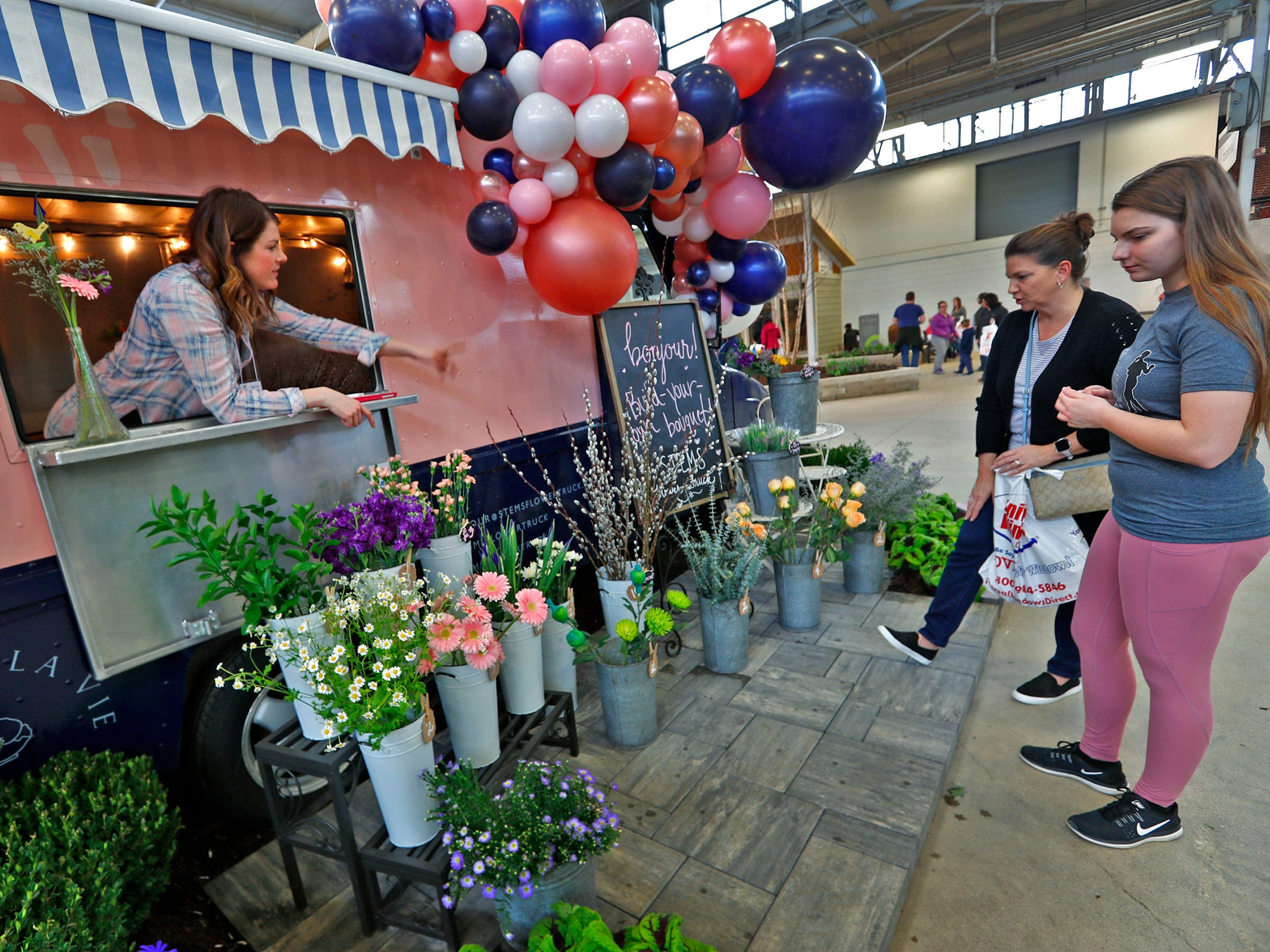 Katie Conway, left, owner of Stemsflowertruck.com, peeks out from her flower truck to point out flowers to Chris Layton, center, and her daughter, Emily Layton at the Indiana Flower + Patio Show, at the Indiana State Fairgrounds, Sunday, March 10, 2019.