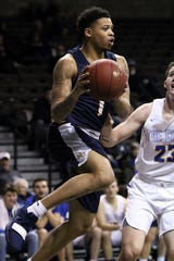 TJ Henderson of Marian looks to pass the ball as Jackson Lamb of Briar Cliff defends during Saturday's NAIA quarterfinal round in Sioux Falls, SD.