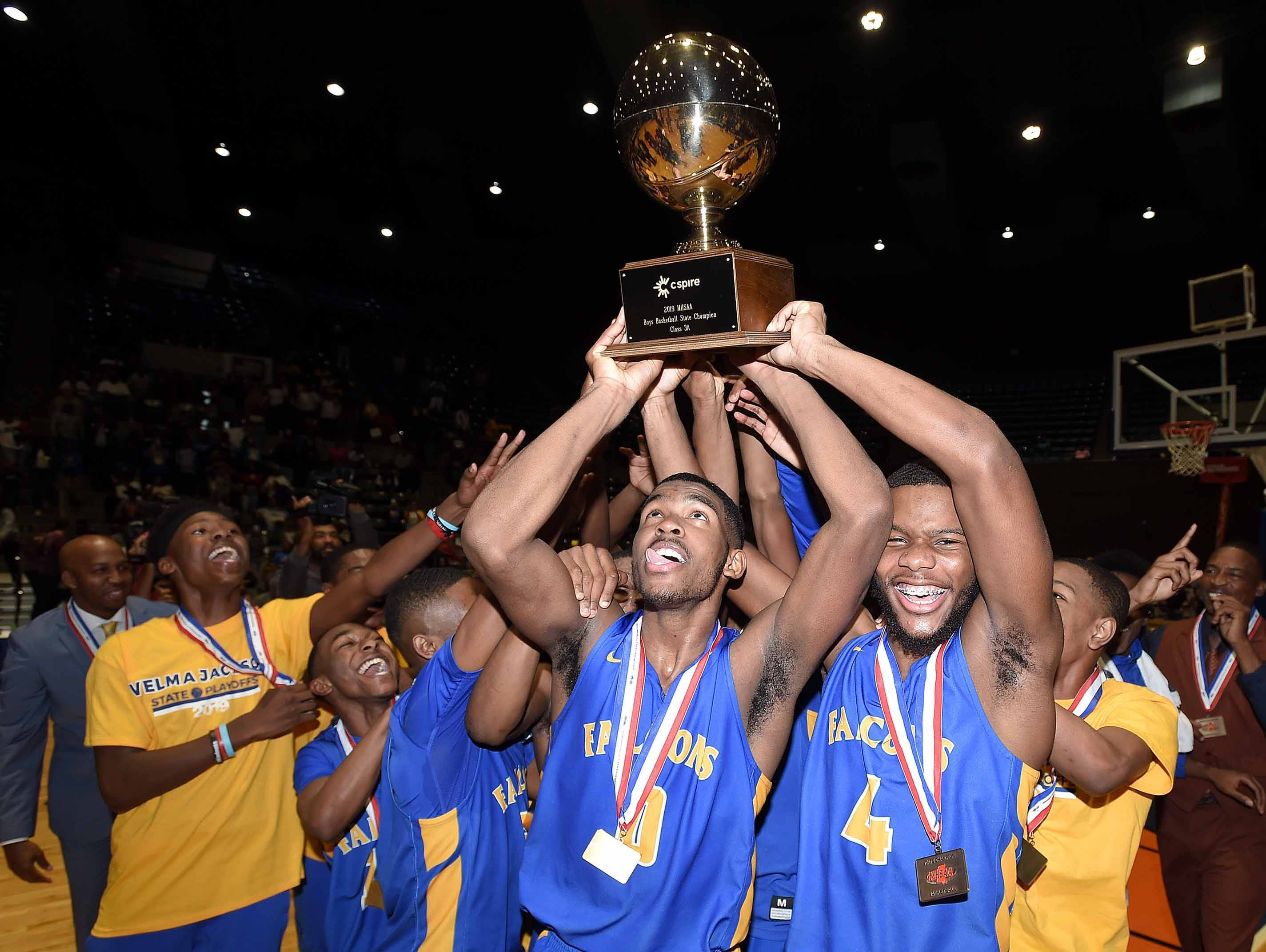 The Velma Jackson Falcons celebrate with the Class 3A trophy after beating Holly Springs in the finals of the MHSAA C Spire State Basketball Championships at the Mississippi Coliseum in Jackson, Miss., on Saturday, March 9, 2019.