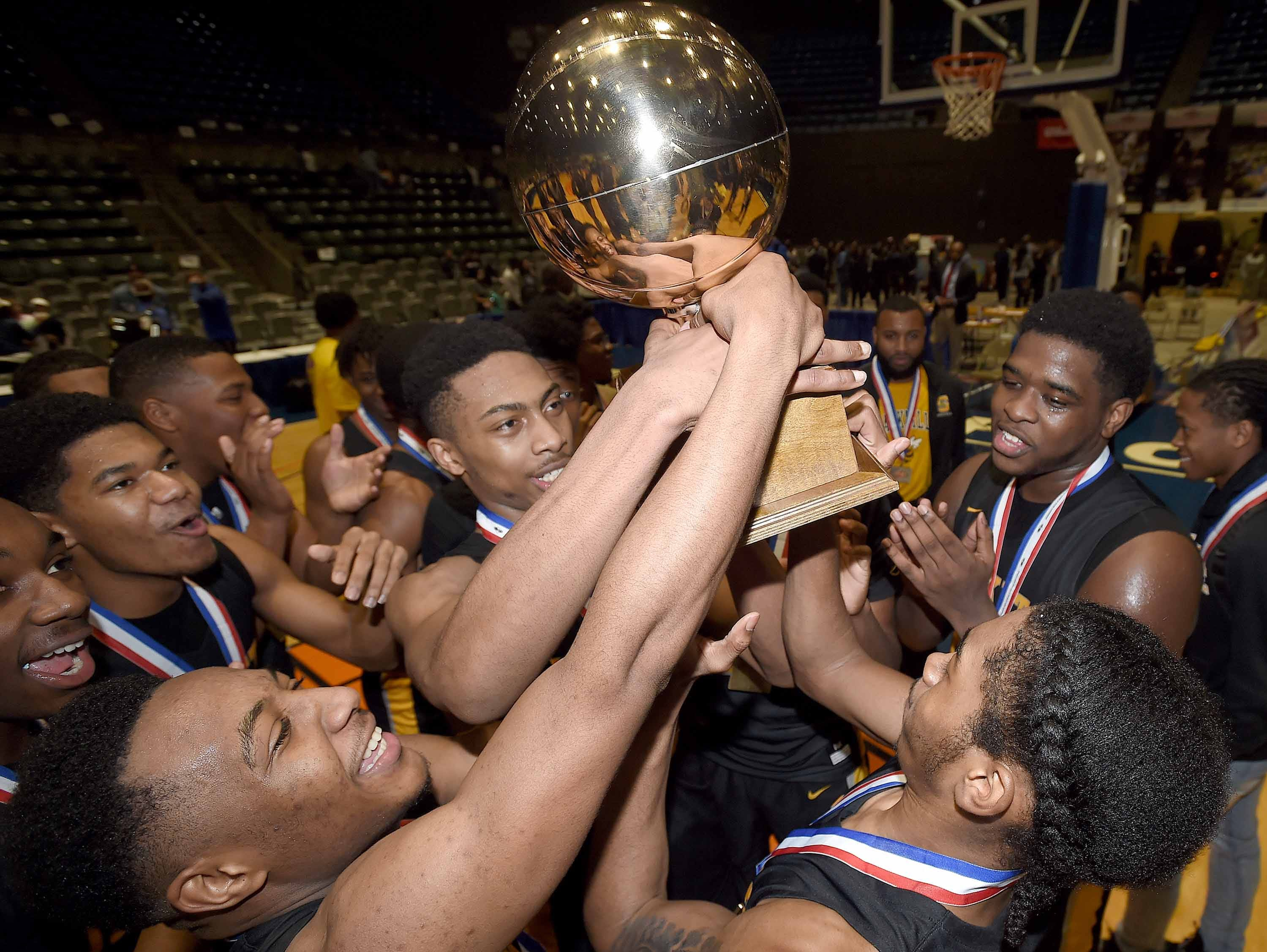 The Starkville Yellow Jackets celebrate with the Class 6A trophy after beating Meridian in the Class 6A finals of the MHSAA C Spire State Basketball Championships at the Mississippi Coliseum in Jackson, Miss., on Saturday, March 9, 2019.