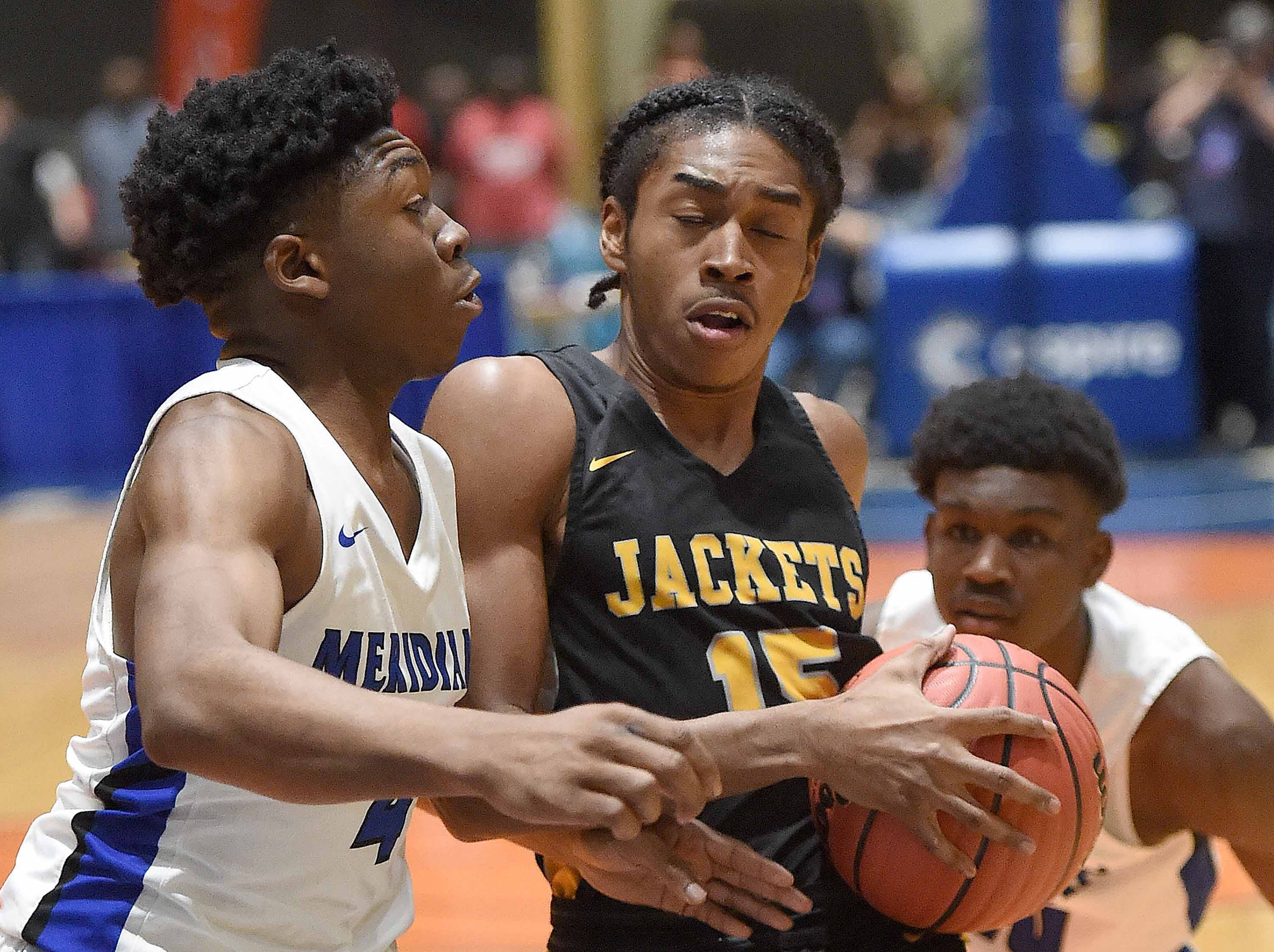 Starkville's Jamarrion Brown (15) tries to split a Meridian's double team in the Class 6A finals of the MHSAA C Spire State Basketball Championships at the Mississippi Coliseum in Jackson, Miss., on Saturday, March 9, 2019.