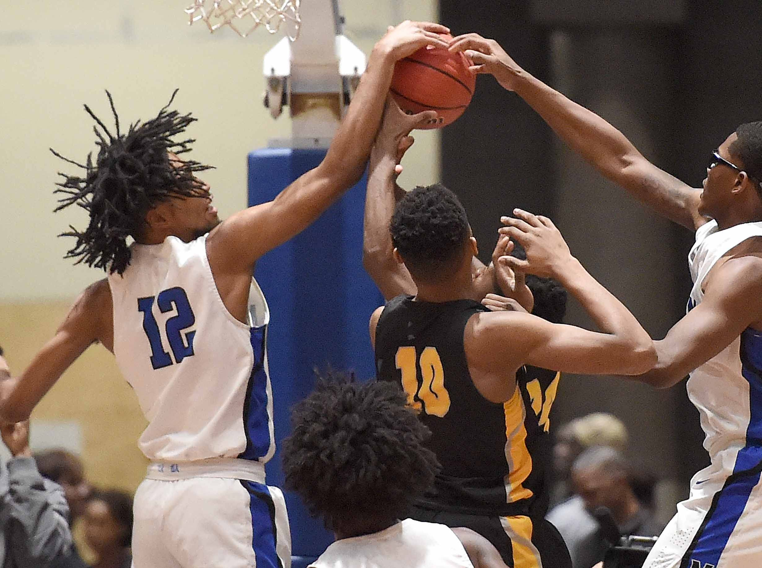 Meridian's Vontrell Pringle (12) and KeEdrick Armstead (25) team up to block a Starkville shot in the Class 6A finals of the MHSAA C Spire State Basketball Championships at the Mississippi Coliseum in Jackson, Miss., on Saturday, March 9, 2019.