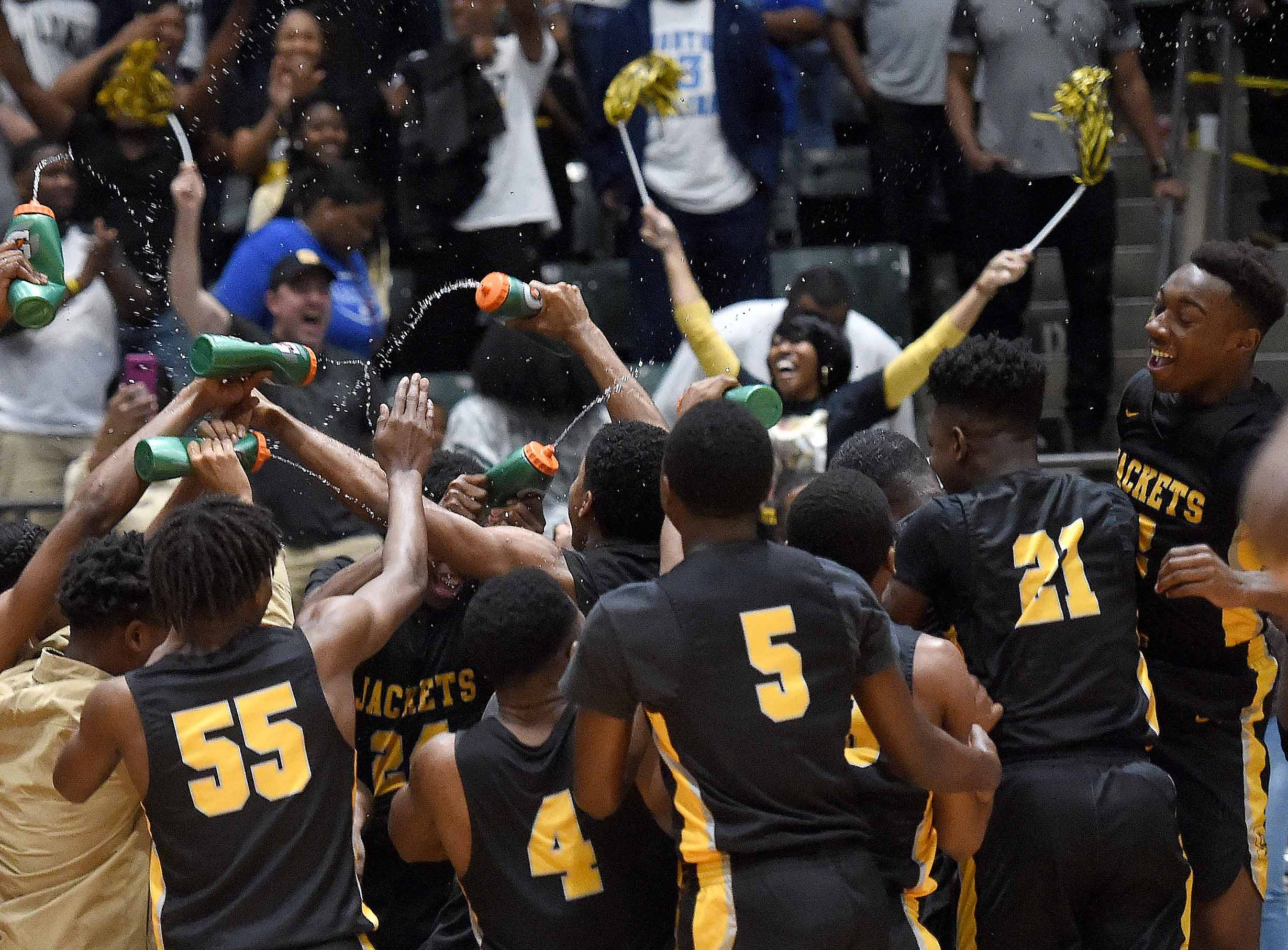 The Starkville Yellow Jackets spray head coach Greg Carter with water bottles after beating Meridian in the Class 6A finals of the MHSAA C Spire State Basketball Championships at the Mississippi Coliseum in Jackson, Miss., on Saturday, March 9, 2019.
