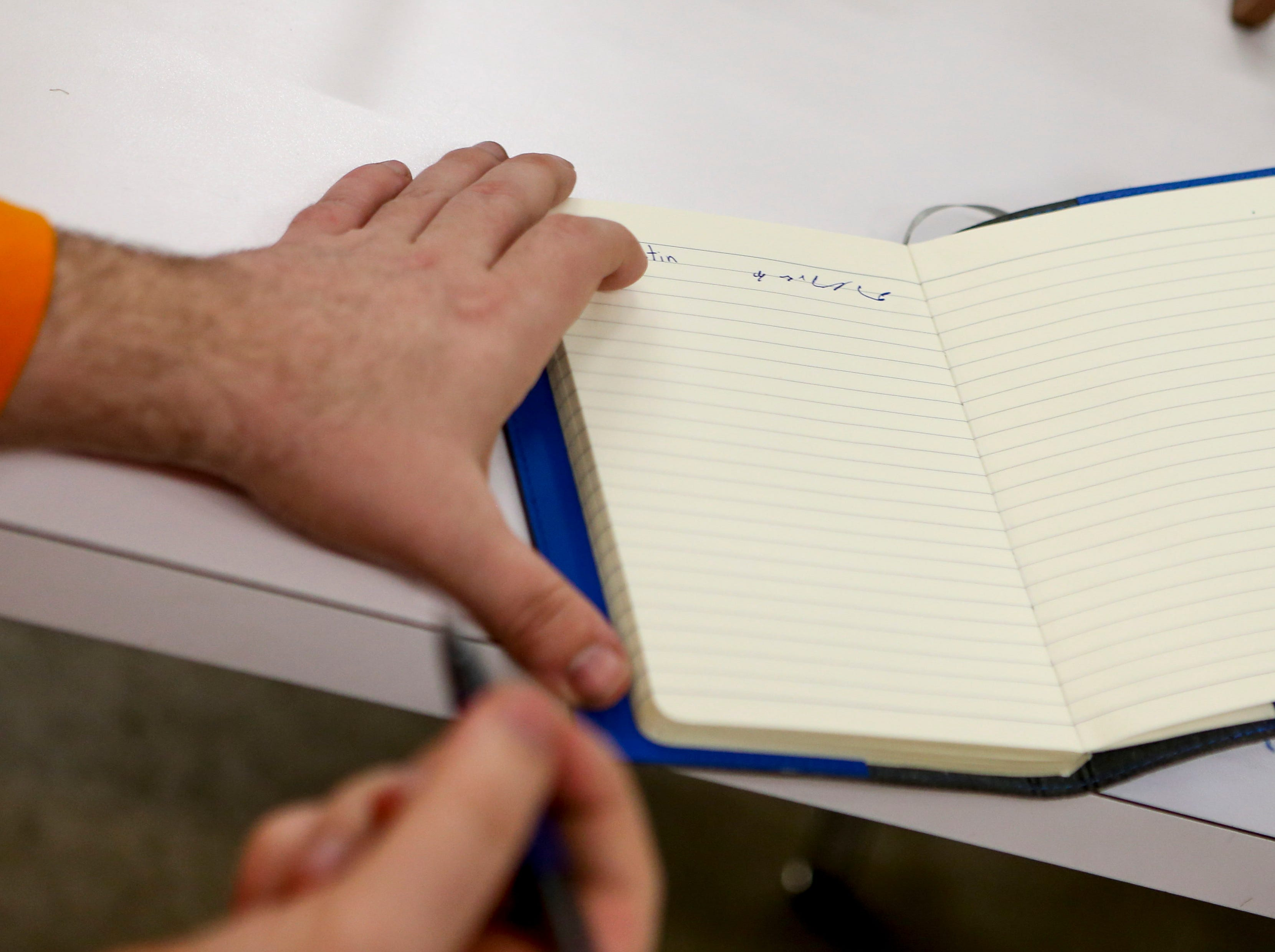 Justin Milford proudly displays his writing in a notebook after classes at McNairy Developmental Services in Selmer, Tenn., on Thursday, Feb. 21, 2019.