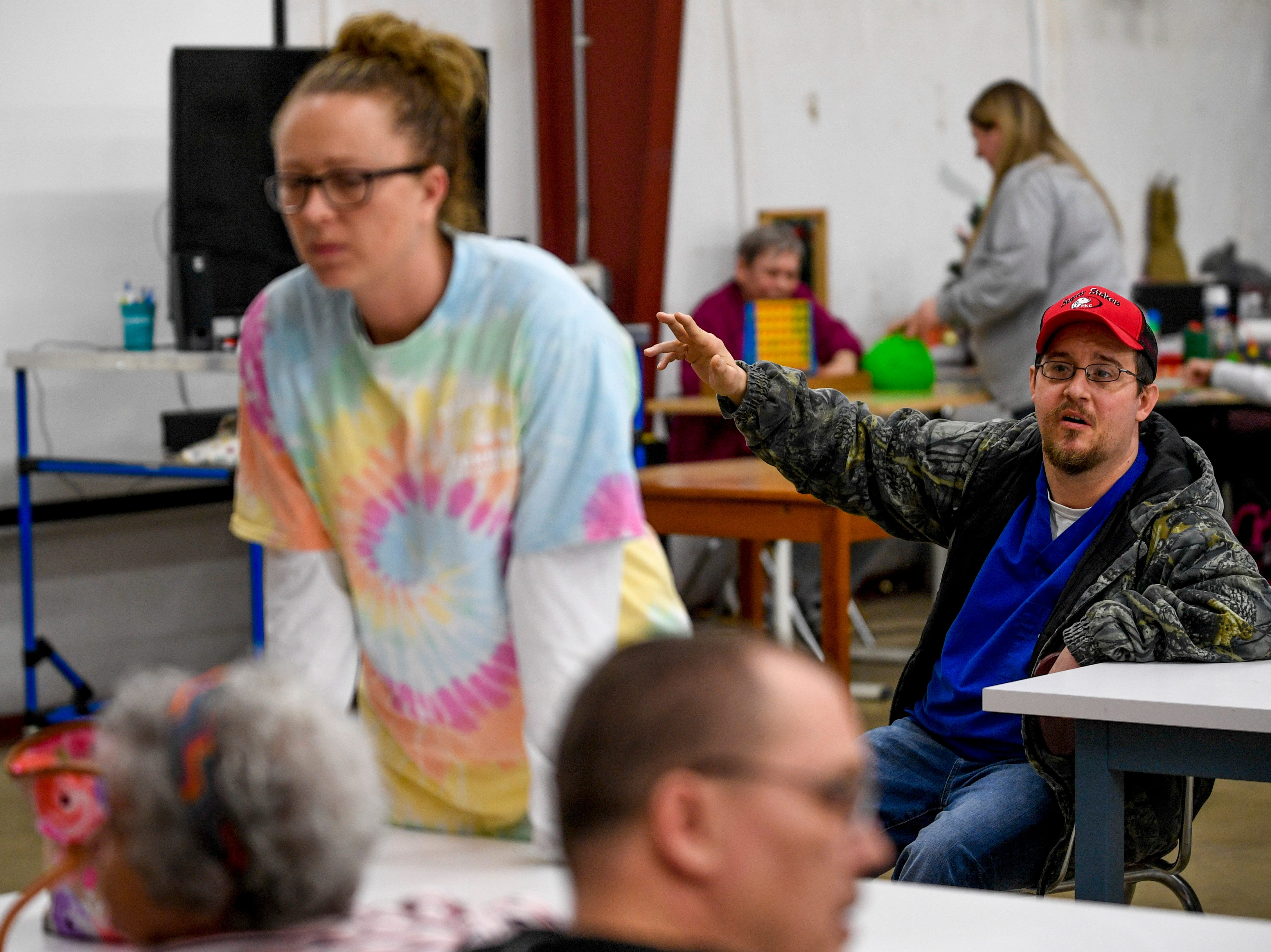 Jon Bailey raises his hand to guess a letter in a game of spelling hangman during classes at McNairy Developmental Services in Selmer, Tenn., on Thursday, Feb. 21, 2019.