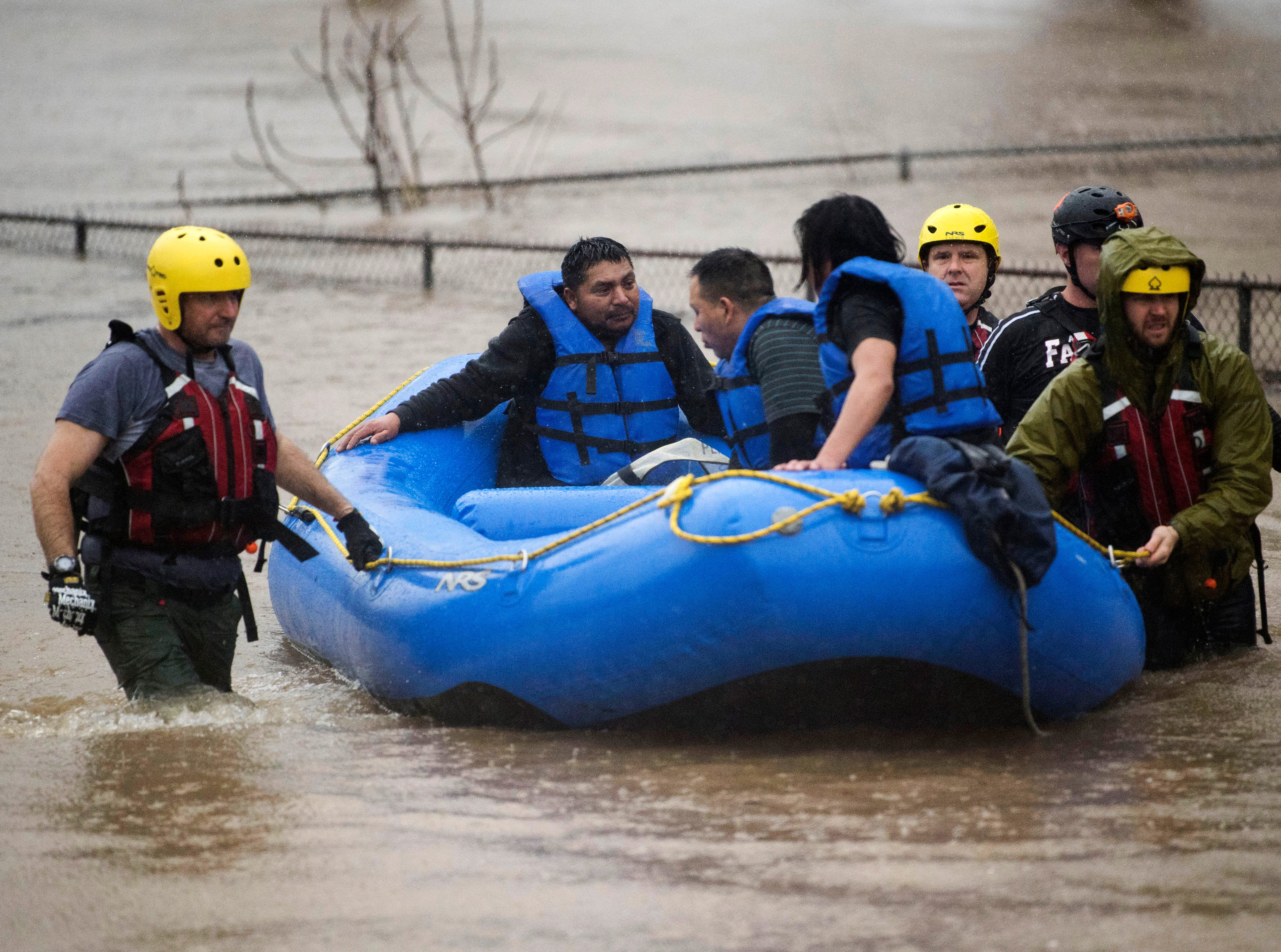 Three men are rescued by the Knoxville Fire Department from a stranded car off of 6th Street in Knoxville Saturday, Feb. 23, 2019.