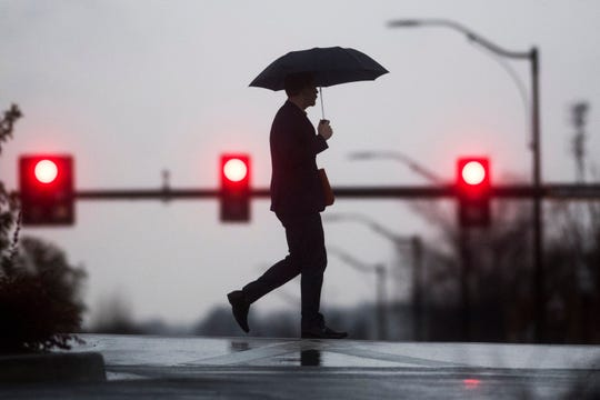 A pedestrian walks through the rain as it falls on University of Tennessee's campus in Knoxville, Wednesday Feb. 20, 2019.