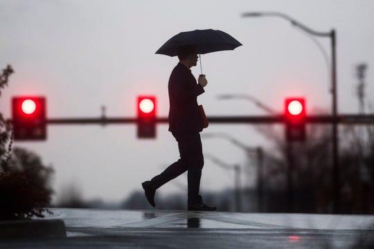Un peatón atraviesa una calle mojada por la lluvia. Foto archivo.