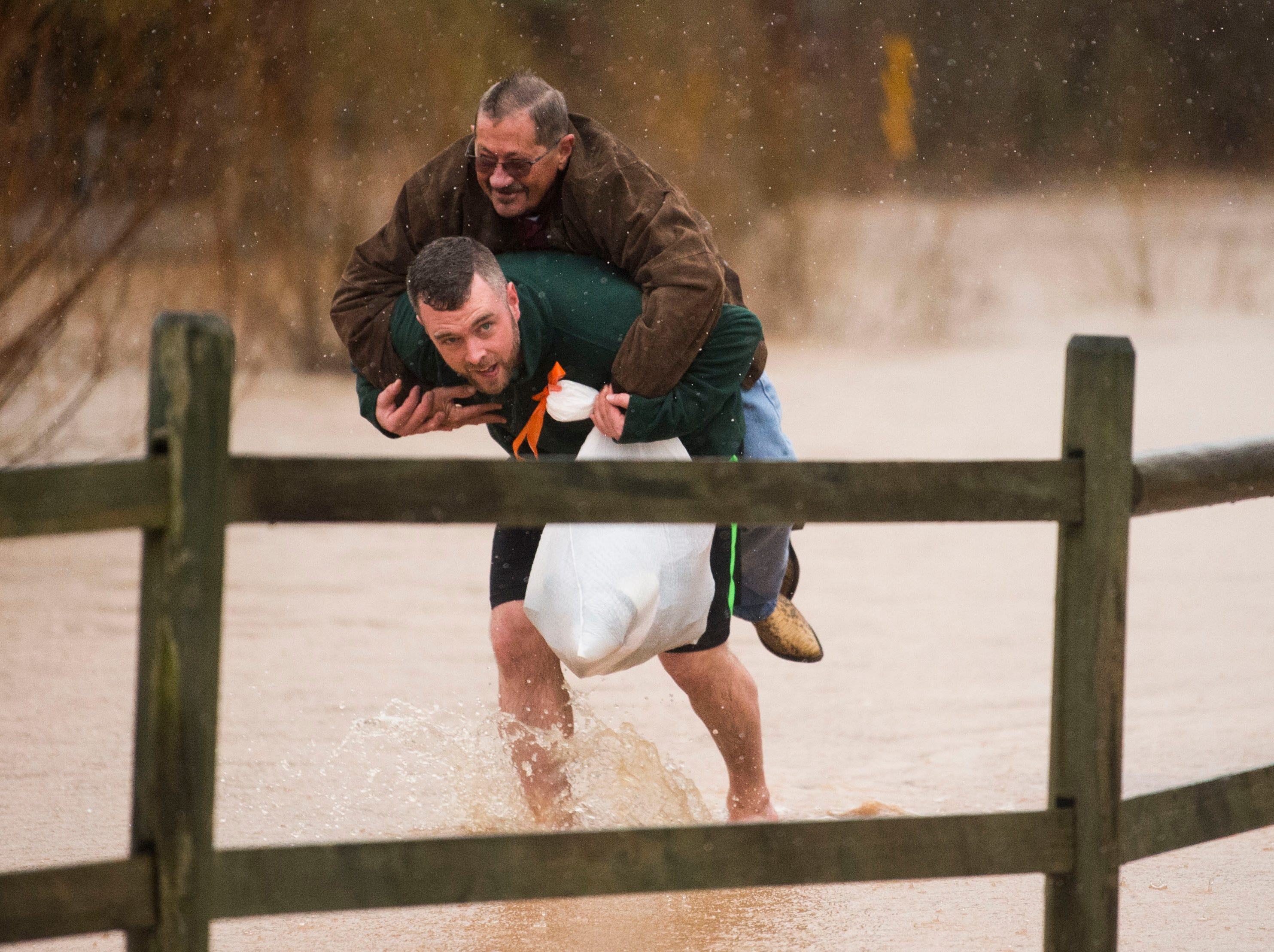 Matt Price gives neighbor Mike Altier a ride on his back through flood waters in Fountain City, Tenn., Saturday, Feb. 23, 2019.
