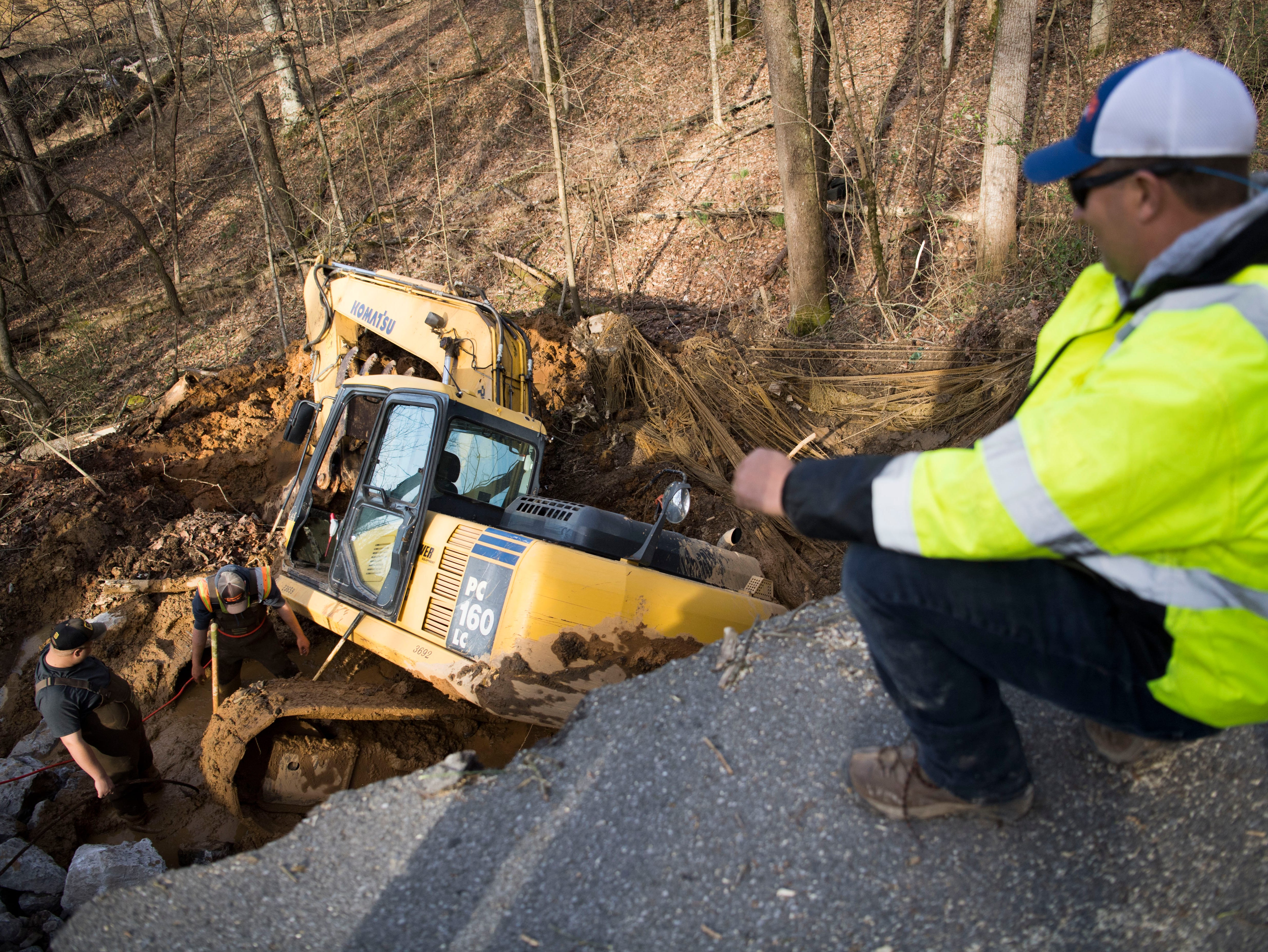Knox County Highway Department employees work to free a backhoe which got stuck in the mud while attempting to repair Everett Road in West Knoxville Monday, Feb. 25, 2019. A combination of the weekend's rain and an underground stream, caused a portion of the road to break away.