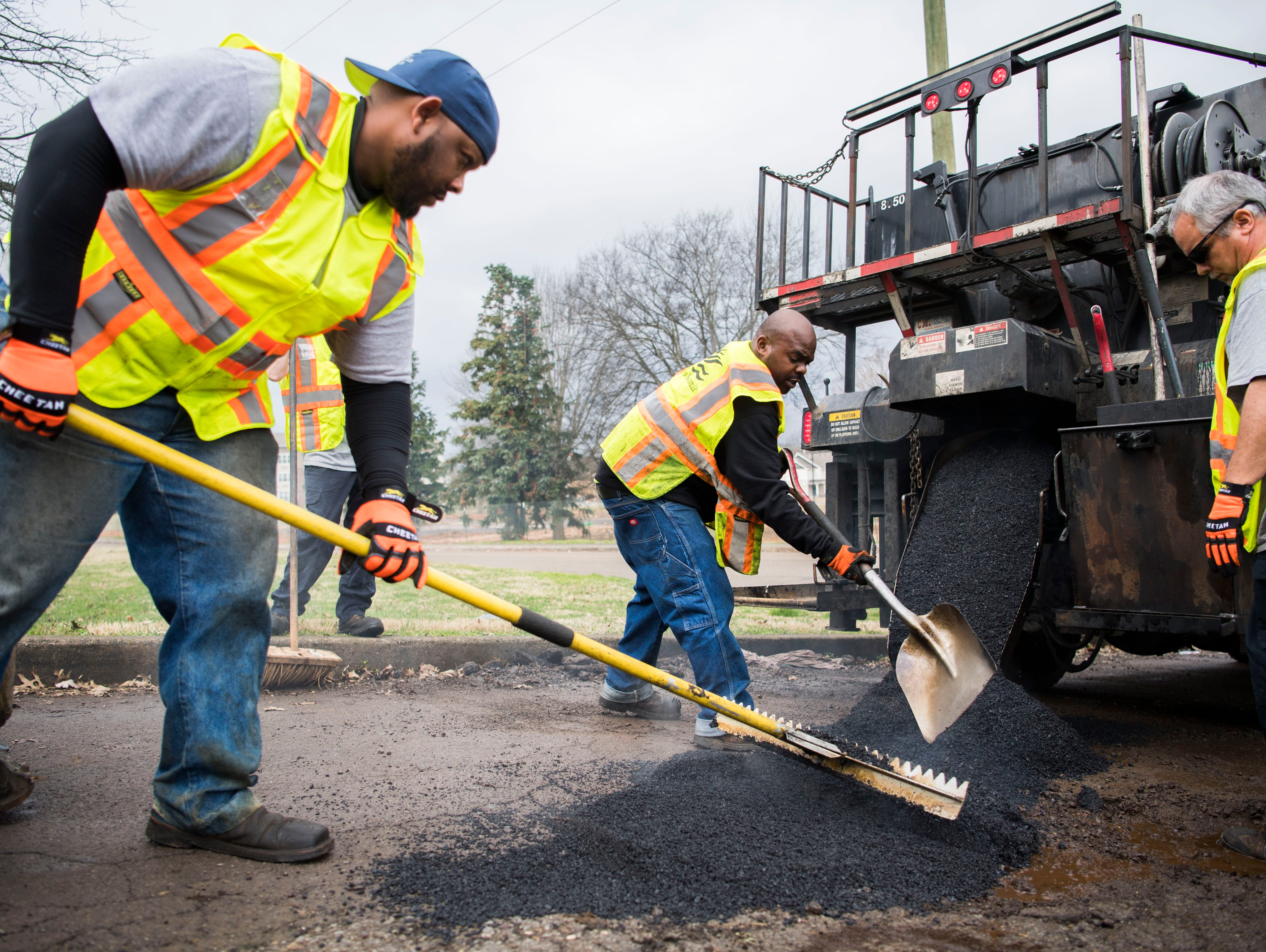 From left City of Knoxville employees Frankie Robinson, Anthony Johnson, and Matt Roth fill potholes for the City of Knoxville, on Sanders Lane in East Knoxville, Thursday, Feb. 7, 2018