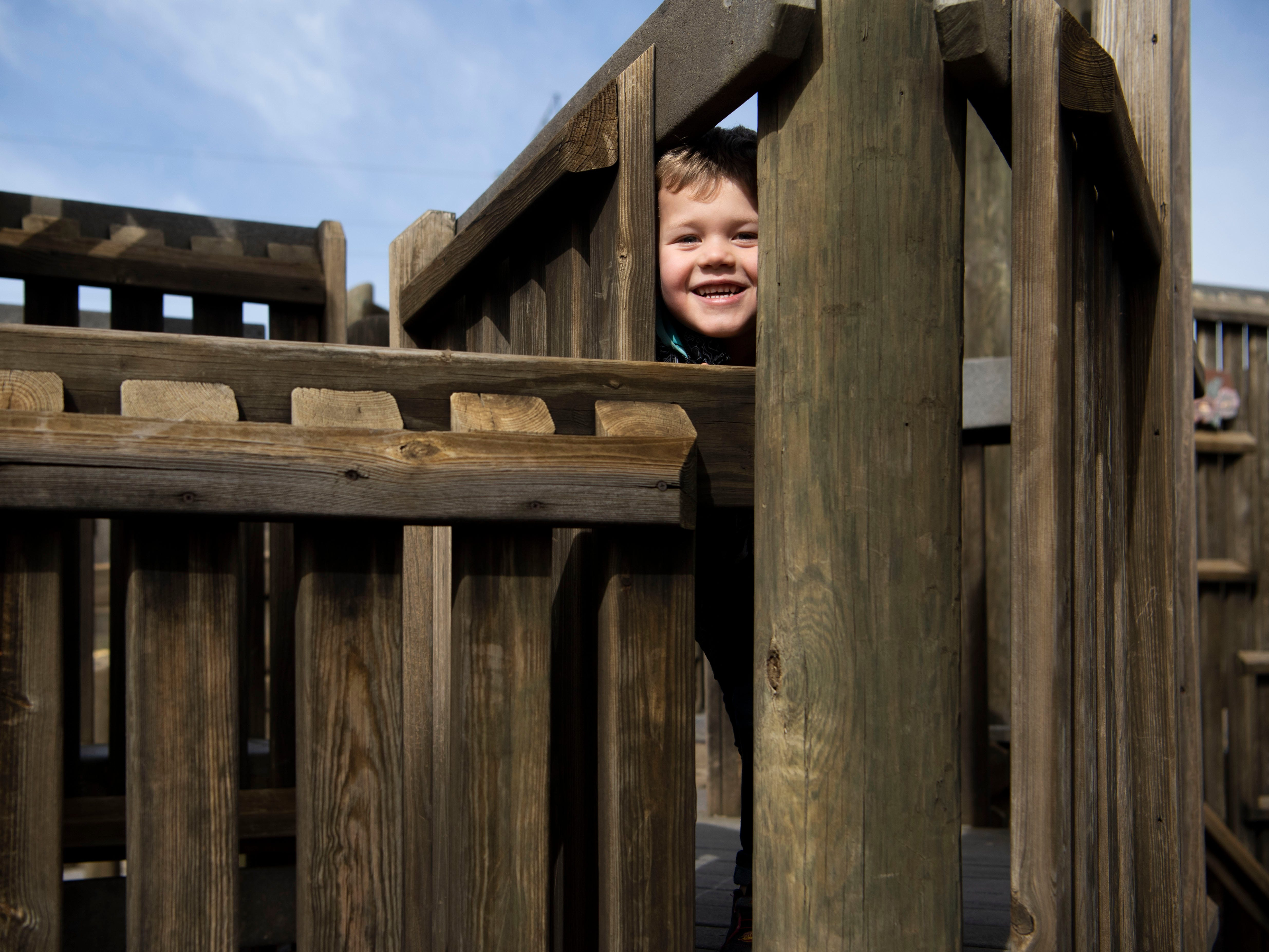 Daemon Nickell, 5, peeks out from between the wooden beams of the  Kids Palace Playground in Clinton, TN on Wednesday, February 13, 2019.