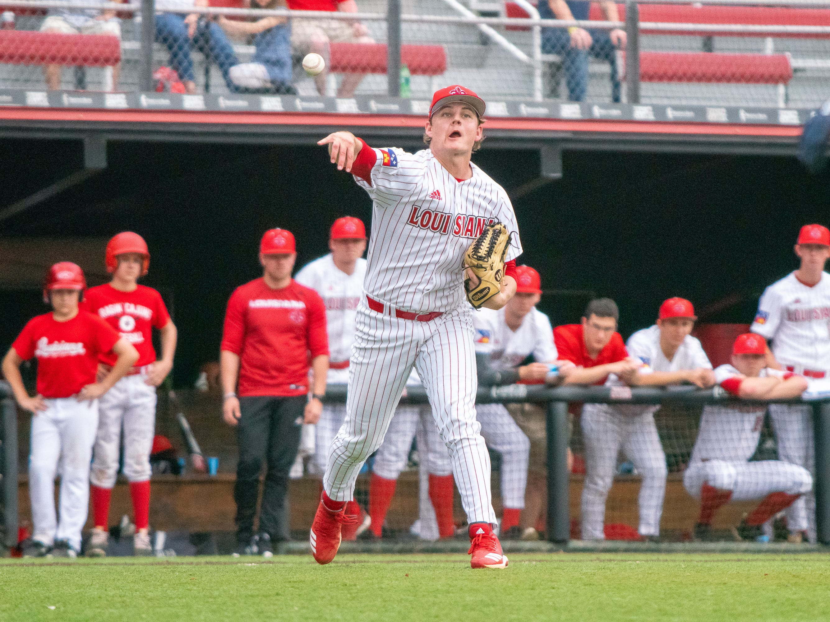 UL's pitcher Blake Schultz throws to first base to get the runner out as the Ragin' Cajuns take on the Loyola Marymount Lions at M.L. Tigue Moore Field on March 10, 2019.