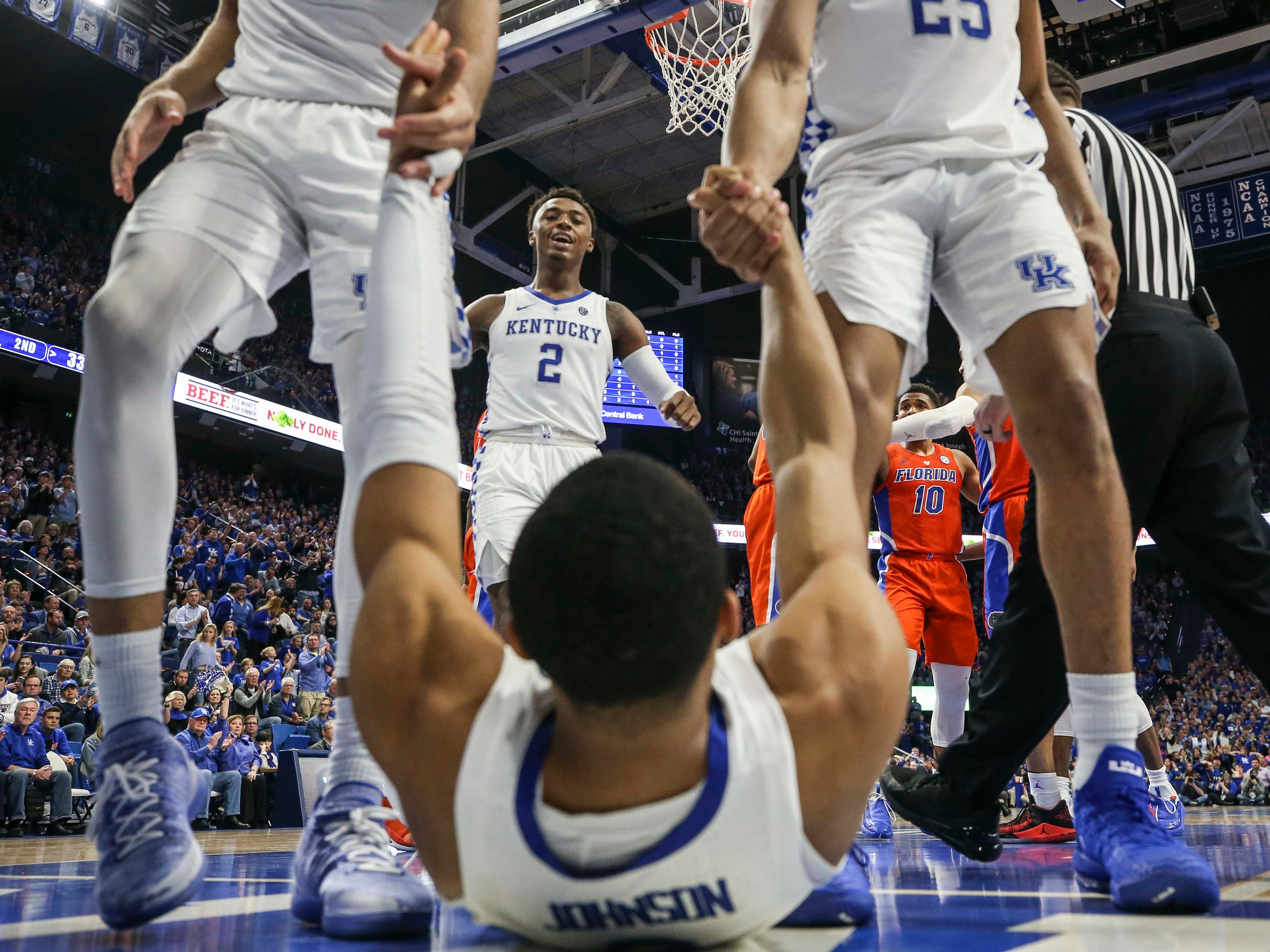 Kentucky's EJ Montgomery and PJ Washington help Keldon Johnson from the floor as Ashton Hagans approaches with a smile during the win against Florida. March 9, 2019