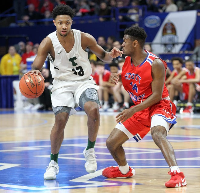 Trinity's David Johnson (13) drives on Scott County's  Glenn Covington (14) during the championship game of the KHSAA Sweet 16 in Lexington, Sunday, March 10, 2019. Trinity won 50-40.