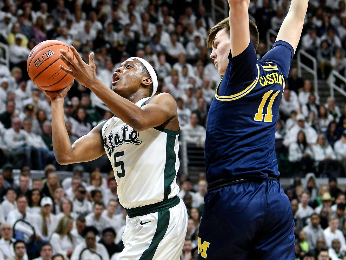 Michigan State's Cassius Winston, left, is fouled while shooting by Michigan's Colin Castleton during the first half on Saturday, March 9, 2019, at the Breslin Center in East Lansing.