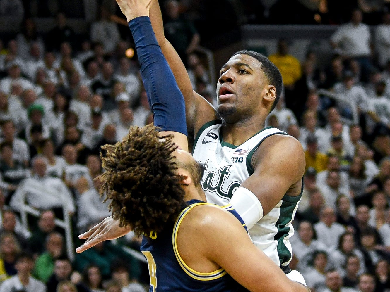 Michigan State's Aaron Henry, right, scores over Michigan's Isaiah Livers during the second half on Saturday, March 9, 2019, at the Breslin Center in East Lansing.
