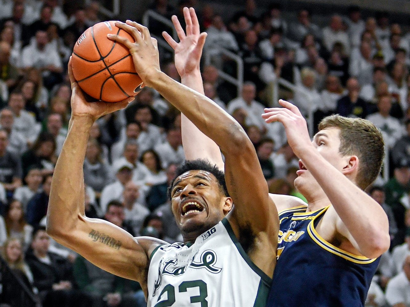 Michigan State's Xavier Tillman, left, is fouled by Michigan's Jon Teske while shooting during the first half on Saturday, March 9, 2019, at the Breslin Center in East Lansing.