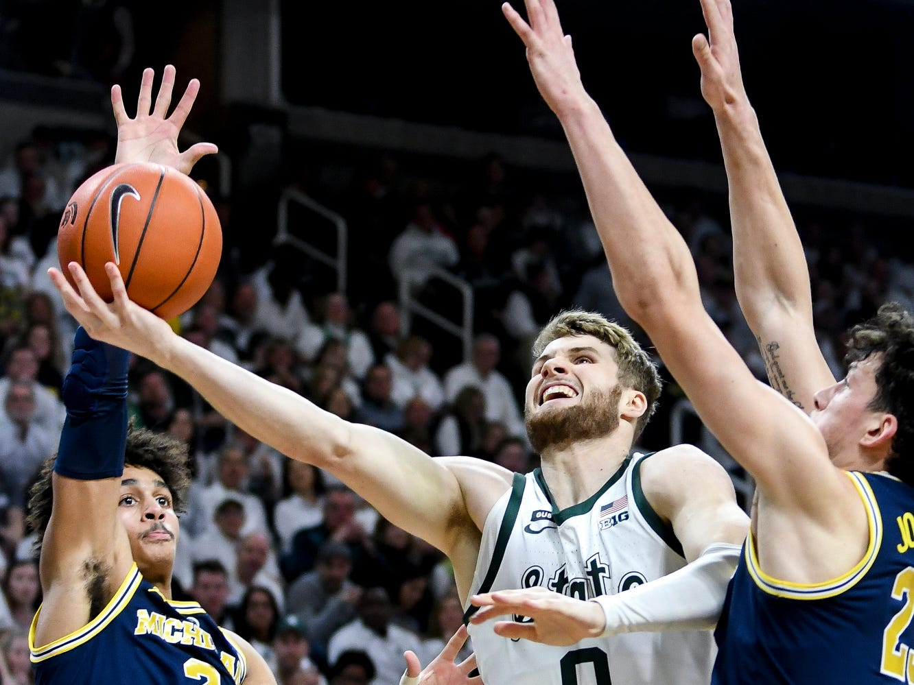 Michigan State's Kyle Ahrens, center, makes a basket between Michigan's Jordan Poole, left, and Brandon Johns Jr. during the first half on Saturday, March 9, 2019, at the Breslin Center in East Lansing.