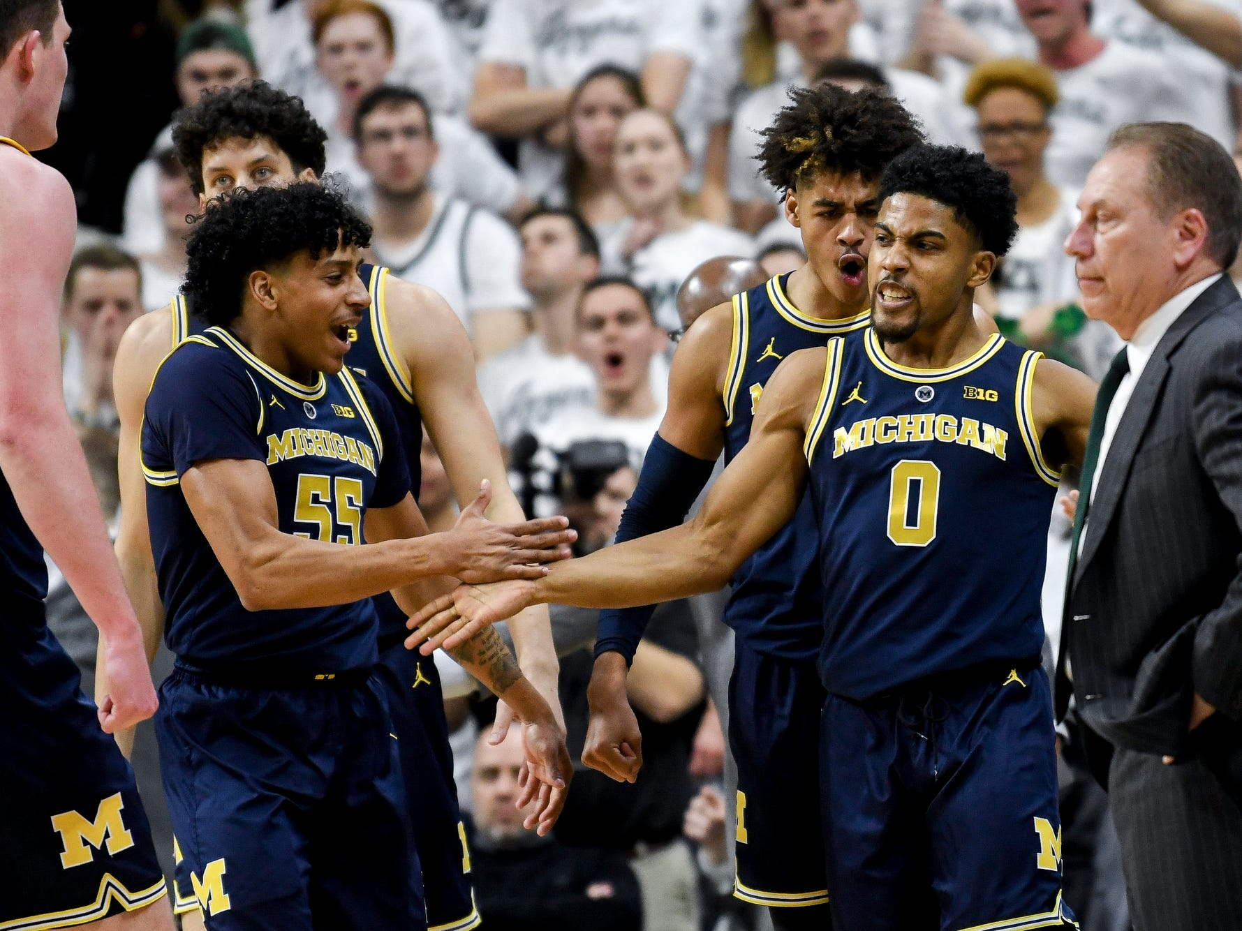 Michigan's David DeJulius, right, celebrates after drawing a MSU foul while shooting during the first half on Saturday, March 9, 2019, at the Breslin Center in East Lansing.