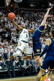 Michigan State's Cassius Winston, left, shoots as Michigan's Colin Castleton defends during the second half on Saturday, March 9, 2019, at the Breslin Center in East Lansing.