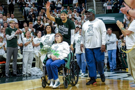 Michigan State senior Kenny Goins, center, waves to the crowd while walking with his family during senior night after the Spartans beat Michigan 75-63 on Saturday, March 9, 2019, at the Breslin Center in East Lansing.