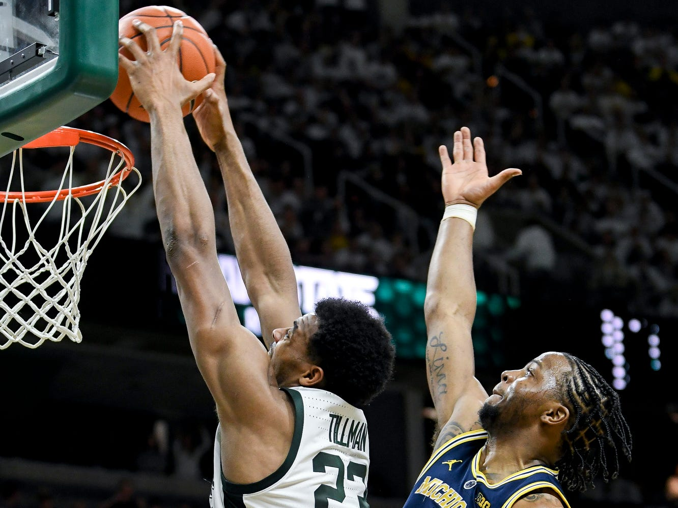 Michigan State's Xavier Tillman, left, dunks as Michigan's Zavier Simpson defends during the first half on Saturday, March 9, 2019, at the Breslin Center in East Lansing.