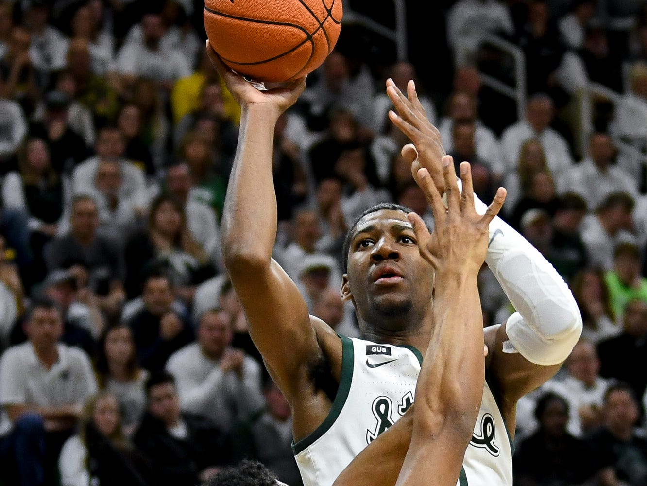 Michigan State's Aaron Henry shoots as Michigan's David DeJulius defends during the first half on Saturday, March 9, 2019, at the Breslin Center in East Lansing.