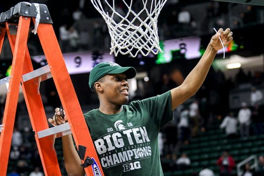 Michigan State's Cassius Winston shows off a piece of the net he cut after the Spartans beat Michigan 75-63 on Saturday, March 9, 2019, at the Breslin Center in East Lansing.