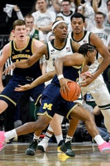Michigan State's Cassius Winston, center, pressures Michigan's Zavier Simpson during the first half on Saturday, March 9, 2019, at the Breslin Center in East Lansing.