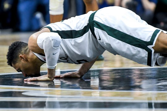 Michigan State senior Kenny Goins kisses the Spartan logo at center court Michigan's during the second half on Saturday, March 9, 2019, at the Breslin Center in East Lansing.