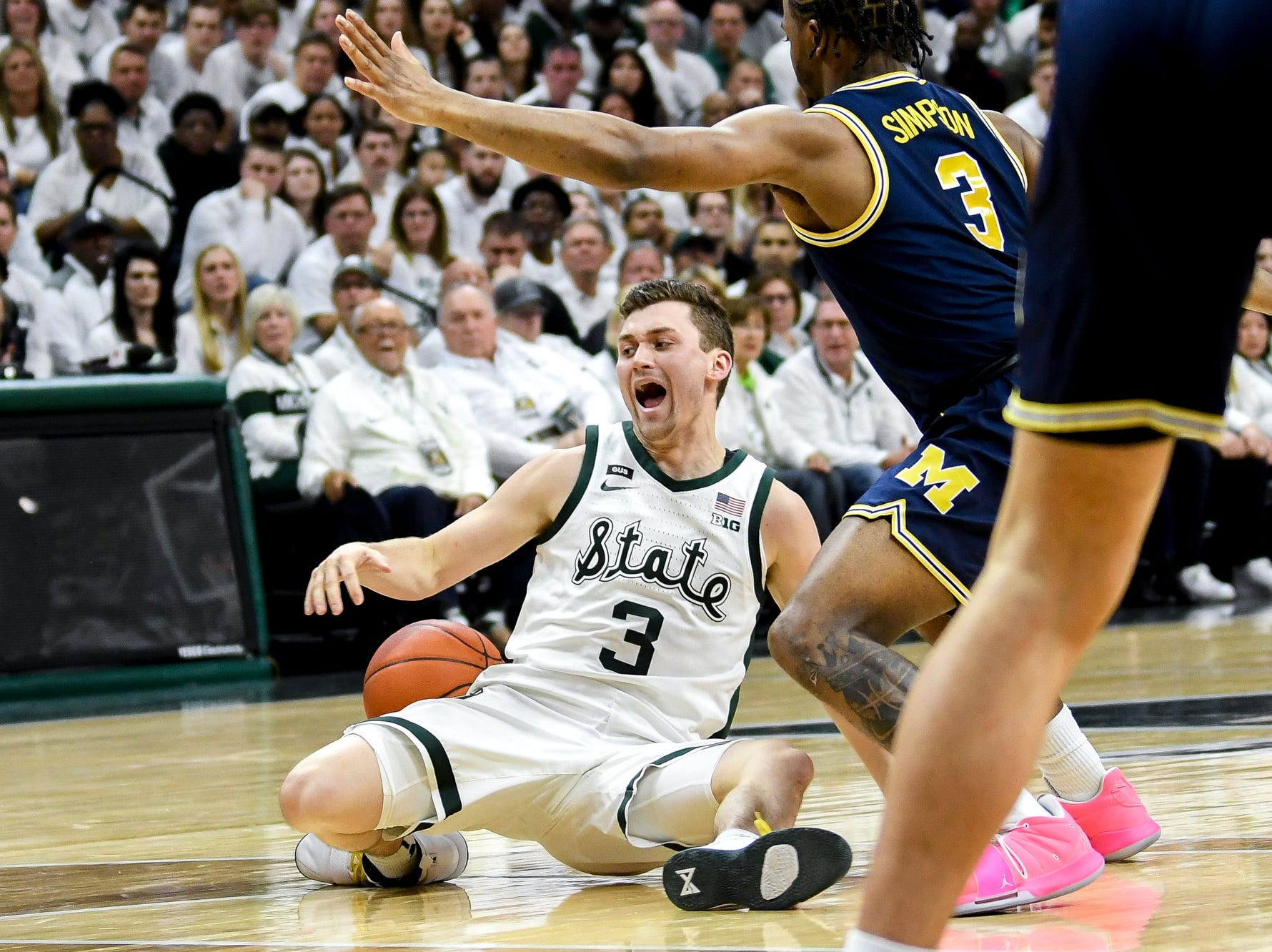 Michigan State's Foster Loyer falls to the ground after drawing a foul on Michigan's Zavier Simpson during the first half on Saturday, March 9, 2019, at the Breslin Center in East Lansing.