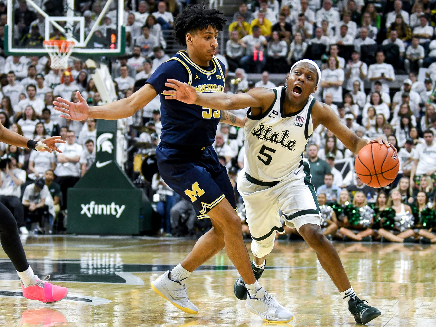 Michigan State's Cassius Winston, right, moves past Michigan's Eli Brooks during the second half on Saturday, March 9, 2019, at the Breslin Center in East Lansing.