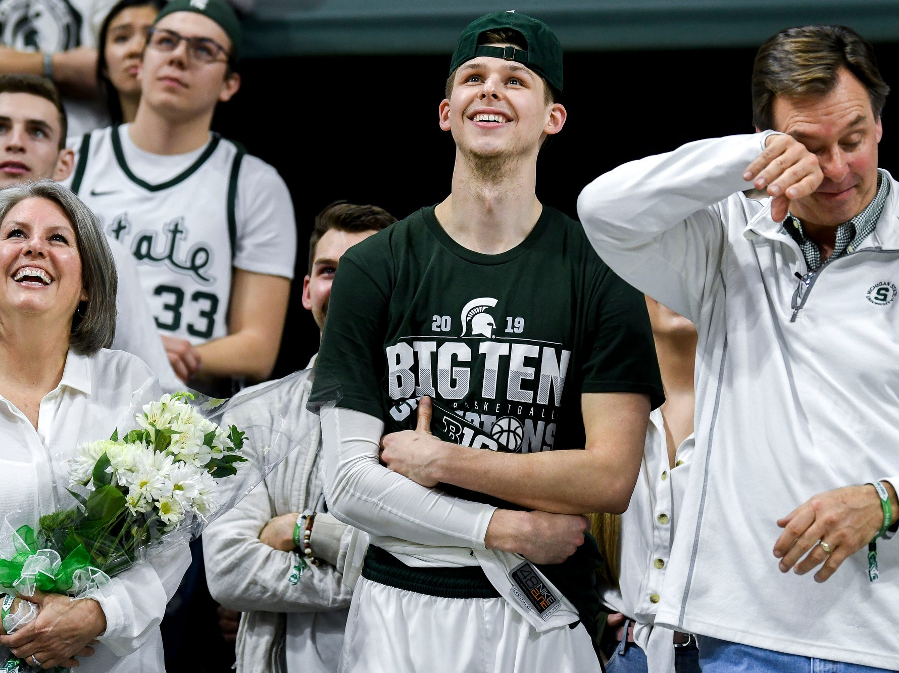 Michigan State senior Matt McQuaid, center, and his family watch a video tribute during senior night after the Spartans beat Michigan 75-63 on Saturday, March 9, 2019, at the Breslin Center in East Lansing.