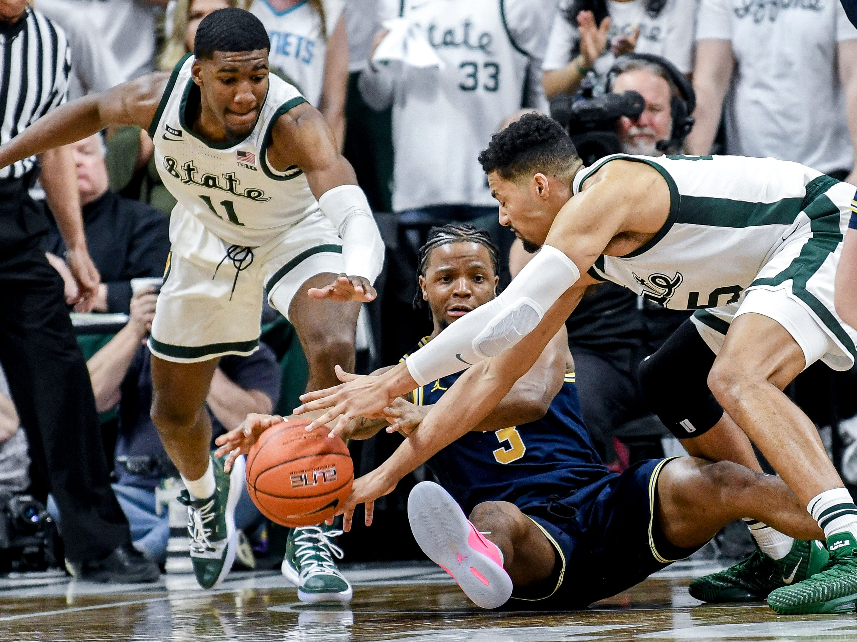 Michigan State's Aaron Henry, left, and Kenny Goins, right, go after the ball after Michigan's Zavier Simpson fell to the floor during the first half on Saturday, March 9, 2019, at the Breslin Center in East Lansing.