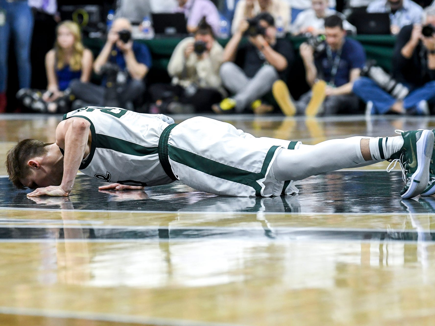 Michigan State senior Matt McQuaid kisses the Spartan logo at center court during the second half on Saturday, March 9, 2019, at the Breslin Center in East Lansing.