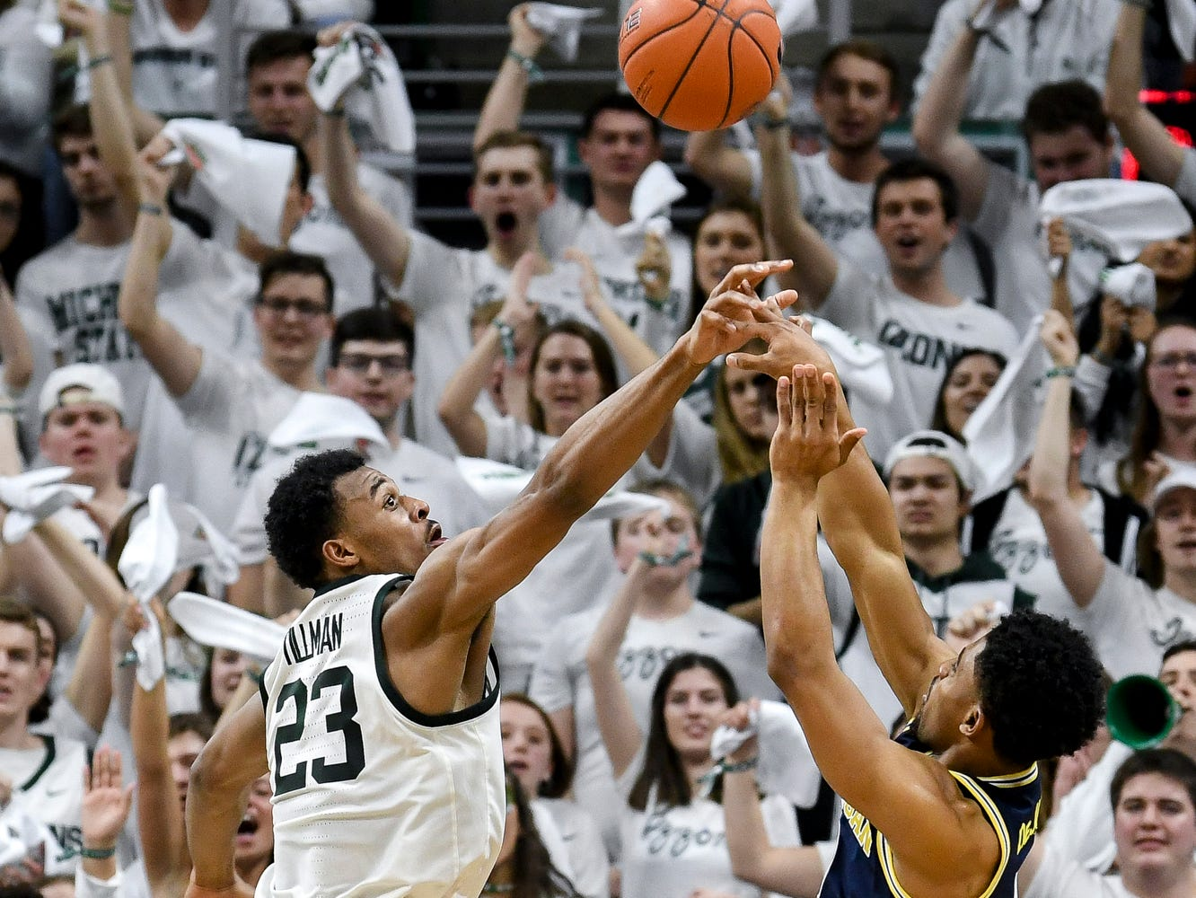 Michigan State's Xavier Tillman, left, blocks a shot by Michigan's David DeJulius during the first half on Saturday, March 9, 2019, at the Breslin Center in East Lansing.