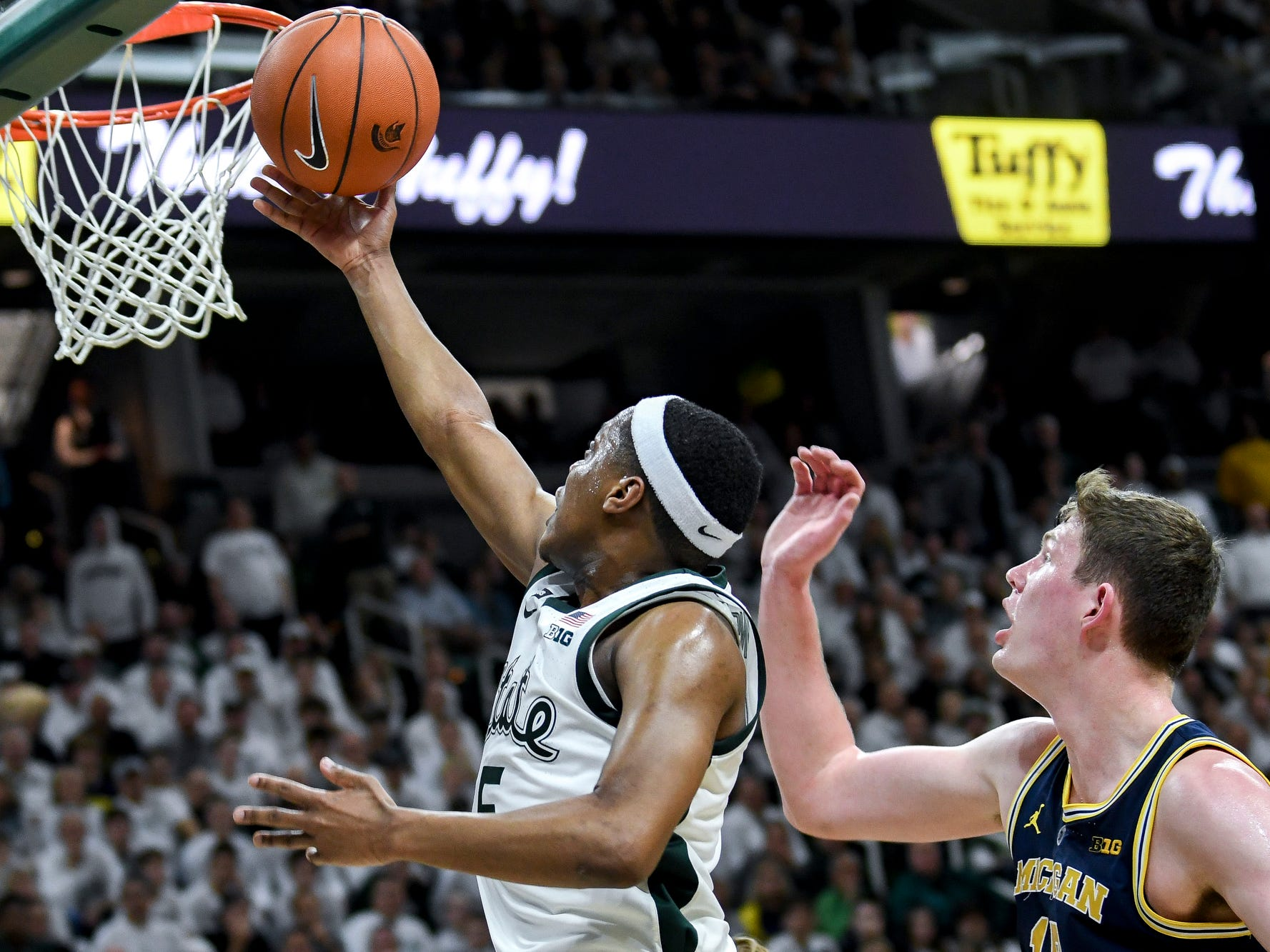 Michigan State's Cassius Winston, left, scores as Michigan's Jon Teske looks on during the second half on Saturday, March 9, 2019, at the Breslin Center in East Lansing.