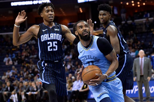 Memphis Grizzlies guard Mike Conley (11) drives past Orlando Magic forwards Wesley Iwundu (25) and Jonathan Isaac in the first half of an NBA basketball game Sunday, March 10, 2019, in Memphis, Tenn. (AP Photo/Brandon Dill)