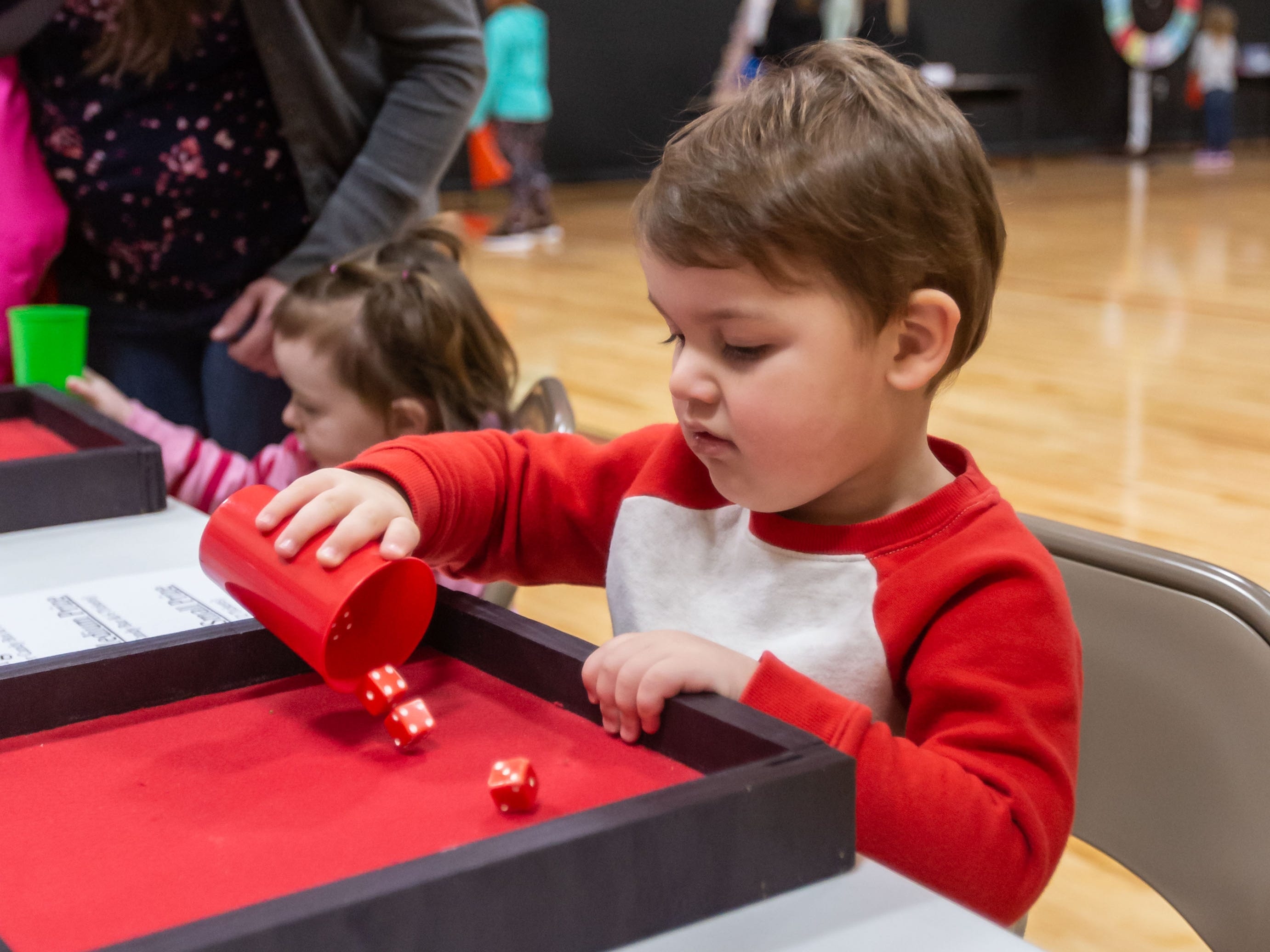 Two-year-old Charlie Scharf of Milwaukee plays a game during the Winter Carnival at St. Matthew's Lutheran School in Oconomowoc on Saturday, March 9, 2019. The event featured a huge prize booth, games, food, a silent auction and more. Proceeds from the Winter Carnival will be used to purchase non budgeted school items.