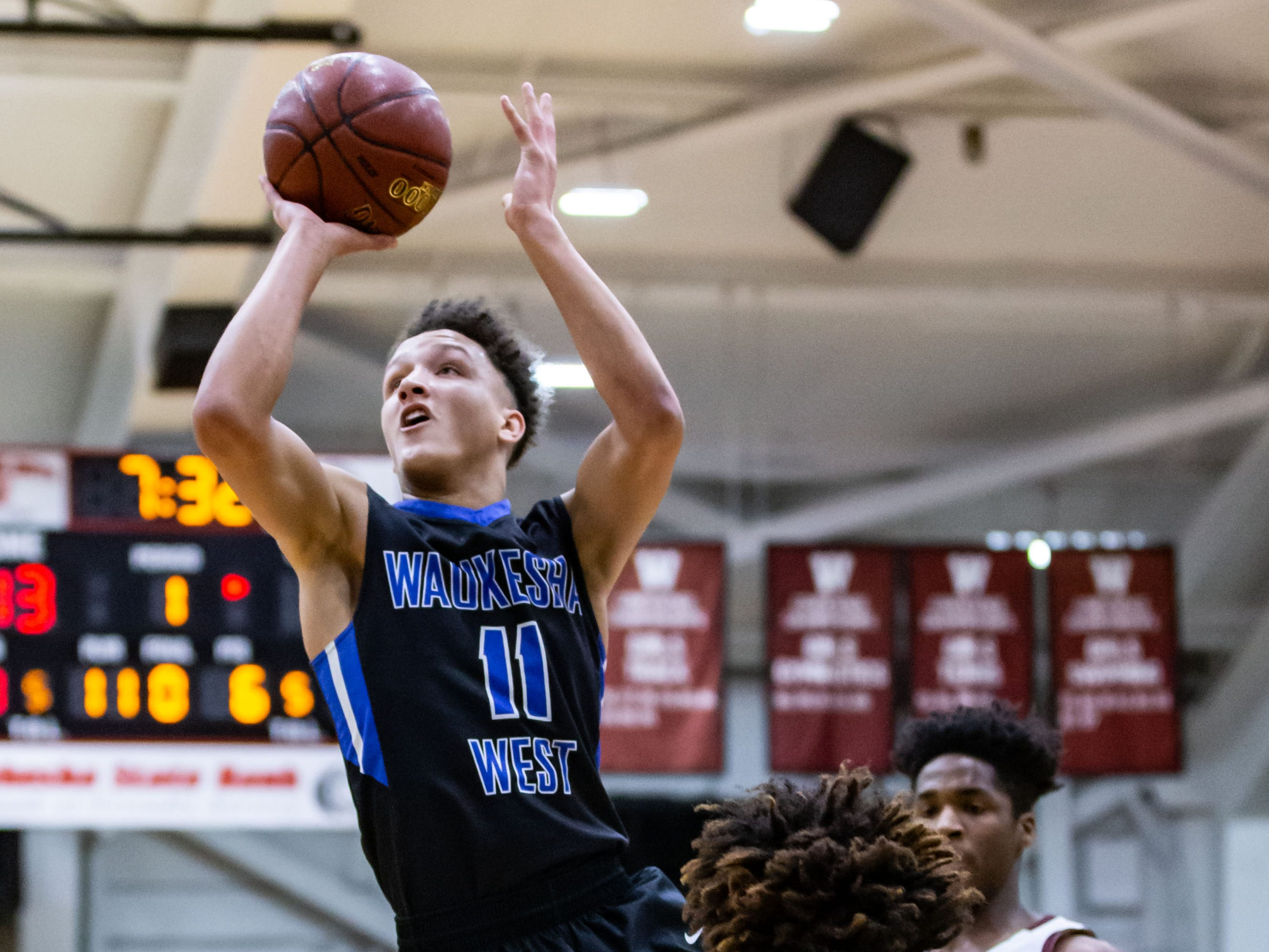 Waukesha West's Cam Palesse (11) takes flight for a shot during the sectional final against West Allis Central at Waukesha South on Saturday, March 9, 2019.