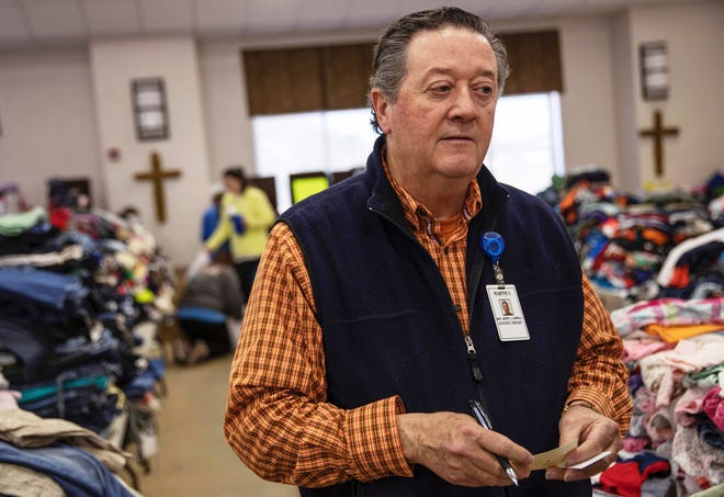 In this Wednesday, March 6, 2019 photo, Rusty Sowell, pastor at Providence Baptist Church, speaks to volunteers organizing donations at the church in Beauregard, Ala. Dealing with the dead became a huge task in a rural Alabama community where nearly two dozen people died in a tornado outbreak. The county coroner, Bill Harris, set up a temporary command post and performed post-mortem exams. He and Sowell then held 17 separate meetings with relatives of the 23 people who died.