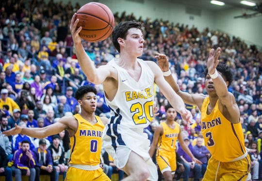 Delta's Josh Greenberg looks for an opening in Marion's defense during their game at Marion High School Saturday, March 9, 2019.