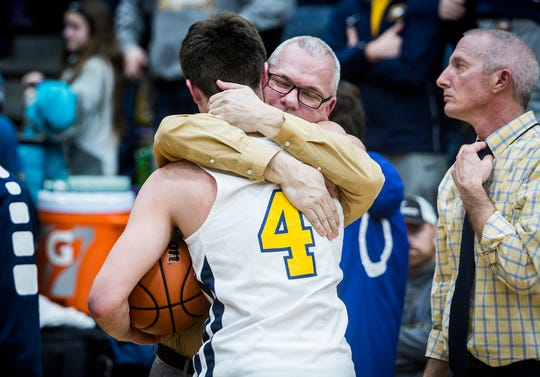 Delta coach Mark Detweiler hugs senior Wesley Woodin after losing to Marion during their game at Marion High School Saturday, March 9, 2019.
