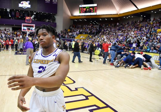 Lipscomb guard Kenny Cooper (21) walks off the court as Liberty celebrates in the background Sunday at Allen Arena.
