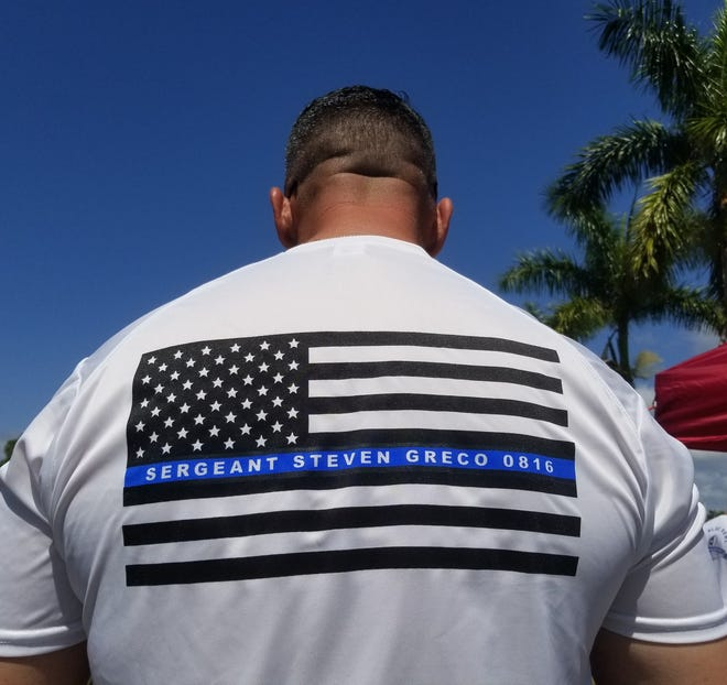 Miccosukee Police Officer Michael Lipari wears a shirt to honor fallen officer Steven Greco, who was killed in a head-on collision Feb. 16, at a fundraiser for Greco's family Sunday, March 10, 2019.