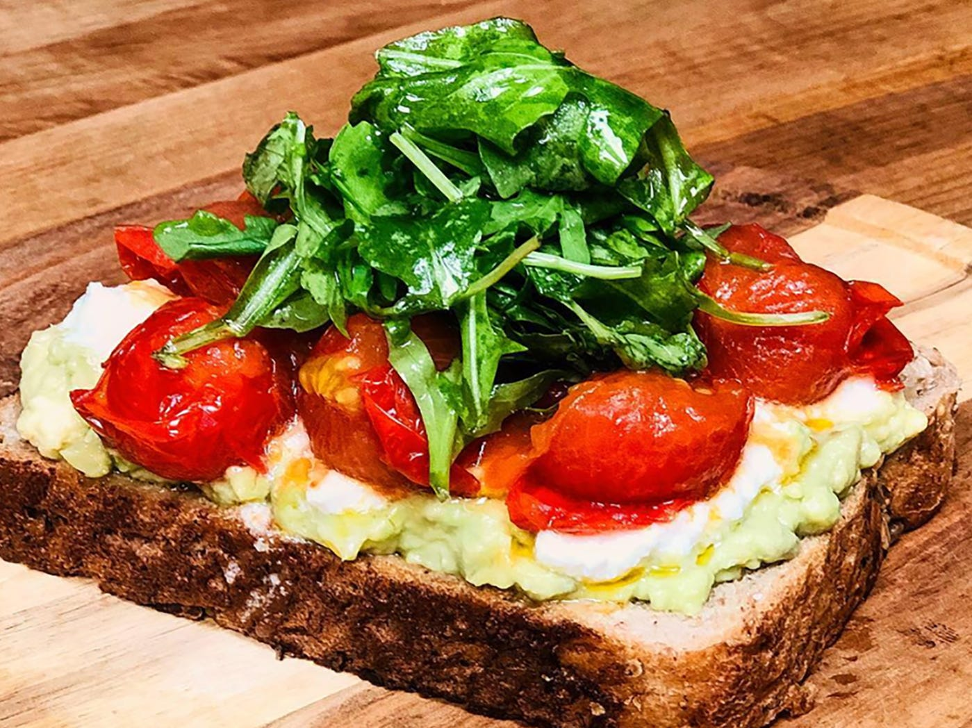 Locale Toast at the new Locale Eatery in North Naples features smashed avocado, roasted cherry tomatoes and ricotta cheese topped with arugula salad.