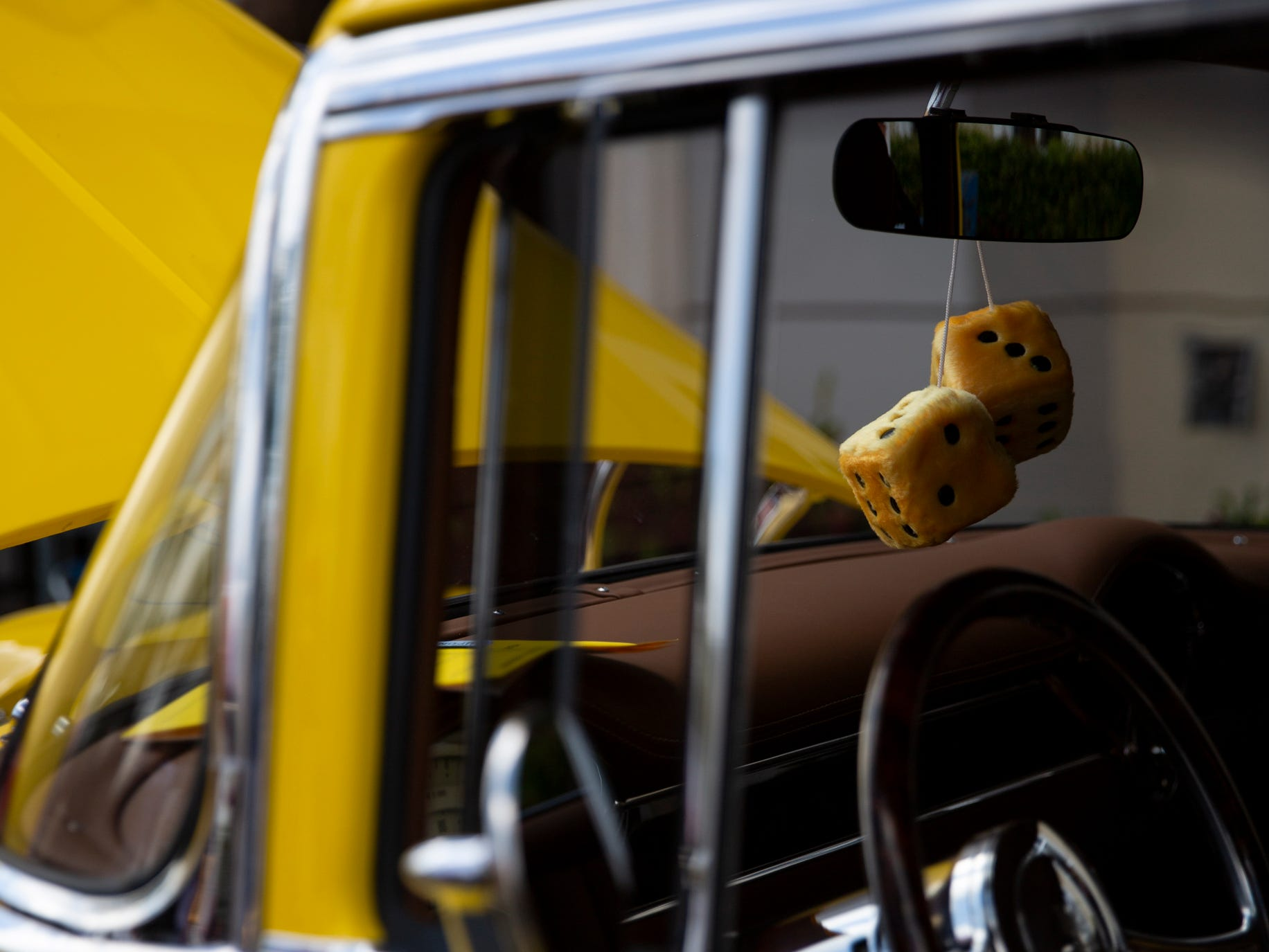 Fuzzy dice hang from the rearview mirror of a 1955 Chevrolet Bel-Air during the West Coast Muscle Car Club's 15th annual car and truck show at the Galleria Shoppes at Vanderbilt in Naples on Sunday, March 10, 2019.