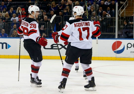 Mar 9, 2019; New York, NY, USA; New Jersey Devils defenseman Damon Severson (28) celebrates with left wing Kenny Agostino (17) after scoring a goal against the New York Rangers during the first period at Madison Square Garden.